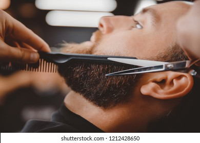 Close-up of barber shearing beard to man in barbershop