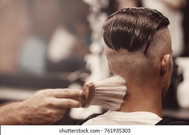 Close-up of barber shop does haircut undercut for man. Concept barbershop. Soft focus.