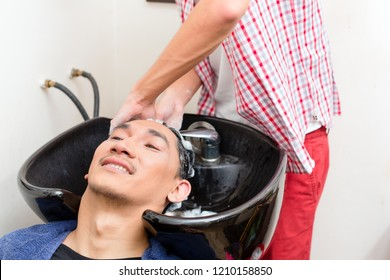 Close-up of barber washing hair in sink at salon