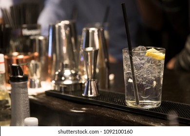 closeup of a barcounter from the barman view. a gintonic is ready to serve. subject and focus on the right