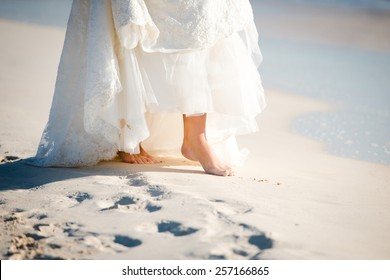 Closeup of bare feet of a bride on the beach in Mexico, Riviera Maya. Destination wedding.