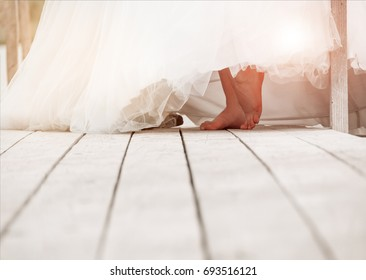 Closeup of bare feet of a bride on a wooden surface. Wedding background with free place for text.