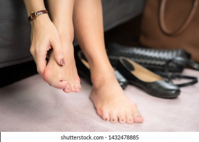Closeup: Bare feet of woman, she massaging to release pain after long day wearing pointy and narrow shoes  -  Medical condition called bunions (Hallux valgus) Woman's health concept - feet problem.