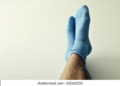 closeup of the bare legs of a young man wearing blue socks with his feet against the wall