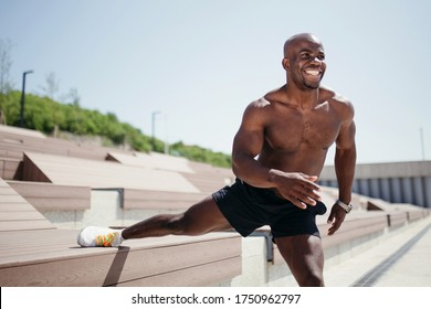 Close-up of a bare-chested African American Pilates trainer doing stretching on the inner thigh muscles and smiling at the camera.