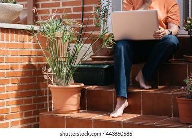 Close-up of barefoot unrecognizable man sitting on steps with laptop