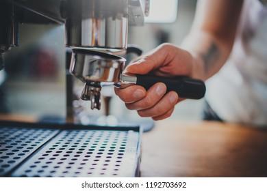 Closeup of barista hand making delicious fresh morning espresso coffee, coffee shop worker holding portafilter for prepare cappuccino