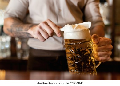 Close-up of barista removing beer froth  while serving beer in a bar.