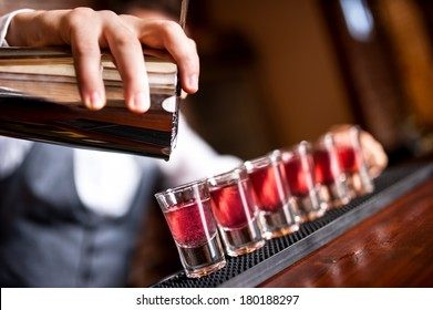 close-up of barman hand pouring alcohol into shot glasses in a nightclub or bar