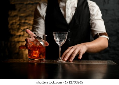 Close-up barman holds glassy mixing cup with strainer full of cold alcoholic drink with pieces of ice. Beautiful empty crystal wineglass stands nearby