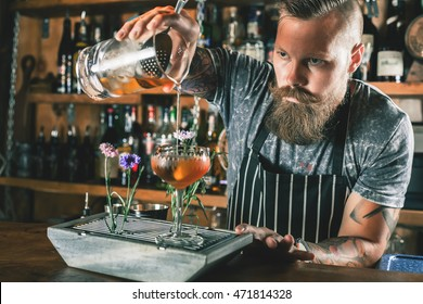 Closeup barman is making cocktail at night club. Unique man. Bartender has a mustache and stylish hairstyle