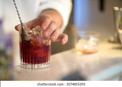 closeup of a barman mixing  a cocktail on a bar counter with a stirring spoon