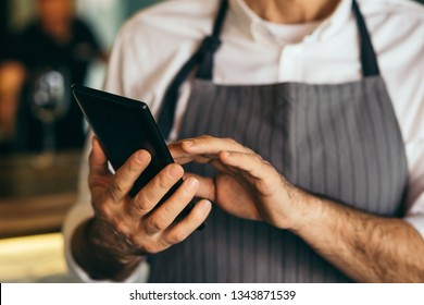 closeup of barman using tablet in cafe bar