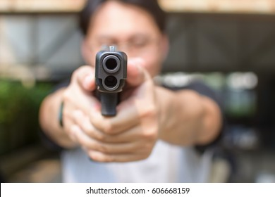 Close-up of the barrel of a pistol pointed at You held by the two hand