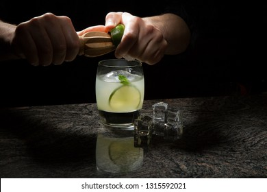Closeup of bartender hands adding lime juice to White Mint Spritzer Cocktail on bar counter.