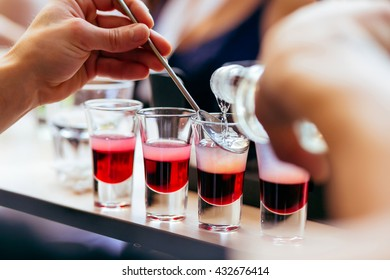 Close-up of bartender hands mixing colored alcohol in liquor shots stemware