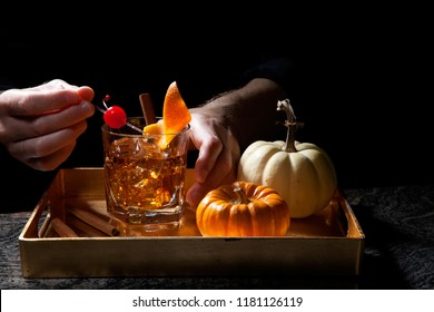 Closeup of bartender hands preparing Old Fashioned Whiskey Cocktail on bar counter. Mini pumpkins and cinnamon sticks. Fall Drinks series.