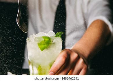 Close-up of bartender preparing Mojito cocktail on a bar counter