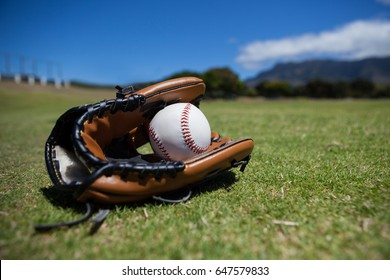 Close-up of baseball and glove on grassy field against sky