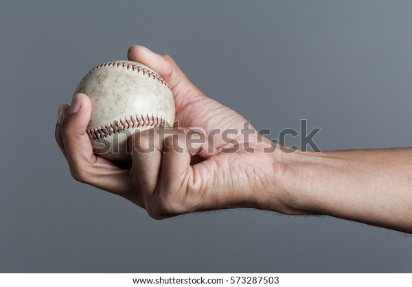 closeup baseball in man's hand, isolated over background
