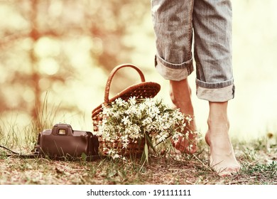 Closeup of basket with white flowers, camera and female legs barefoot in jeans