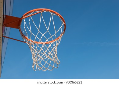 Closeup basketball hoop, basket with white net and blue sky in background