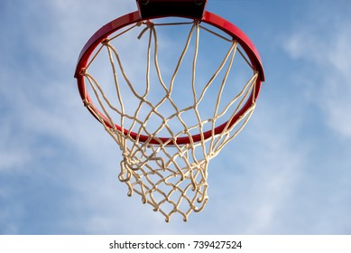 close-up of a basketball hoop with the blue sky in the background