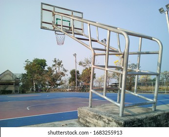 Closeup of Basketballhoop structure and the basketball court. On the background of trees and blue sky.