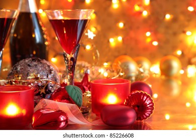 Closeup of bauble, candle lights  and red wine in glasses on gold background with lights.