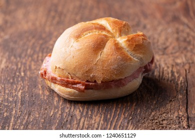 closeup of a bavarian leberkaese bun on dark wood