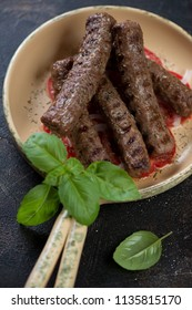 Closeup of bbq traditional balkan cevapi or skinless beef sausages in a serving pan, vertical shot, selective focus