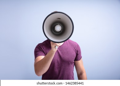 Close-up Of A Beard Man Shouting Through A Megaphone Against Gray Background
