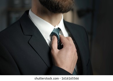 Closeup of bearded businessman hand in black suit adjusting checkered tie