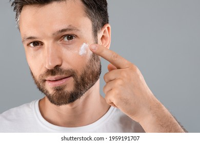 Closeup of bearded handsome man applying face cream on grey studio background, copy space. Good looking middel aged man using beauty products for his face, moisturising or nourishing skin