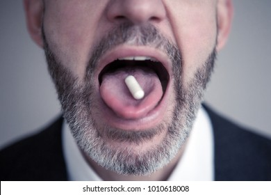 closeup of bearded man with pill on his tongue