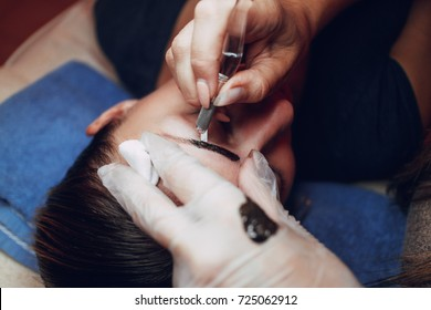 Closeup of a beautician hands microblading eyebrows to model with tool
