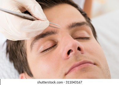 Close-up Of Beautician Hands Plucking Handsome Man Eyebrows With Tweezers