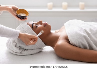 Closeup of beautician holding bowl with face mask next to sleeping black lady at spa salon
