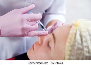 Close-up of a beautician injects Botox injection into the cheekbones of a young woman to correct the form in the medical office