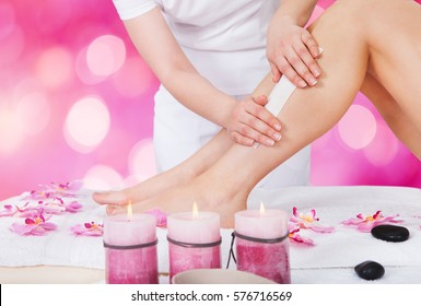 Close-up Of A Beautician Waxing Woman Leg With Wax Strip At Beauty Spa