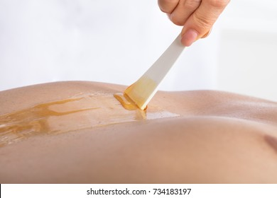 Close-up Of A Beautician's Hand Applying Wax On Man's Chest