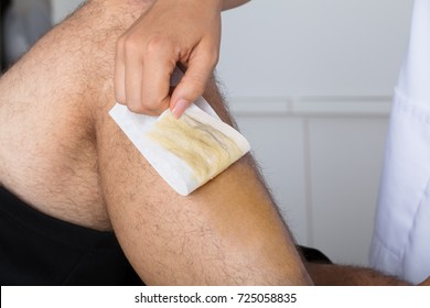 Close-up Of A Beautician's Hand Waxing Man's Leg