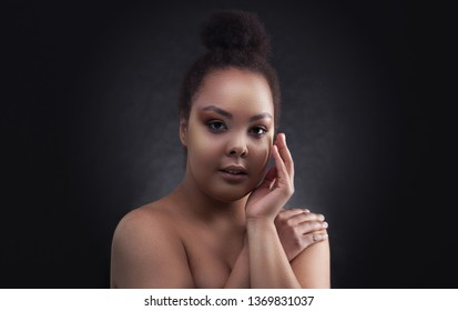 close-up Beautiful black african woman face studio portrait. day makeup. on the dark background.
