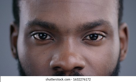 Close-up of beautiful black man eyes staring at camera. Portrait detail of serious confident african american man.