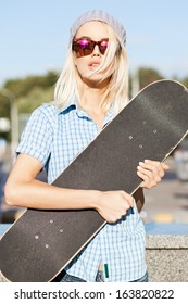 Close-up of beautiful  blond girl in beanie hat and leopard sunglasses who hugs skateboard on sunny day in the street