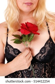 Closeup of a beautiful blond woman in black lingerie holding a red rose, isolated for white background.