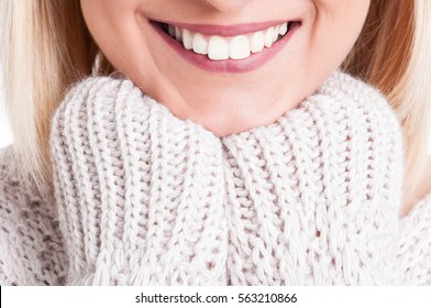 Close-up of beautiful blonde girl smile wearing warm sweater isolated on white background