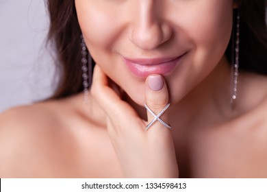 Closeup beautiful brunette girl with long hair in modern silver jewelry earrings, rings, bracelet, chain, necklace. Сoncept shooting for store gentle, elegant, delicate, romantic bijouterie on model