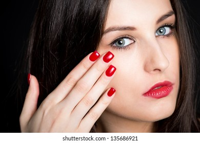 Closeup of beautiful brunette with red nails, black background