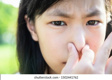 Closeup beautiful child girl pinching nose with disgust on his face due to bad smell,something stinks,female teenager gesture squeezing nose with fingers and looking at camera,bad smell situation